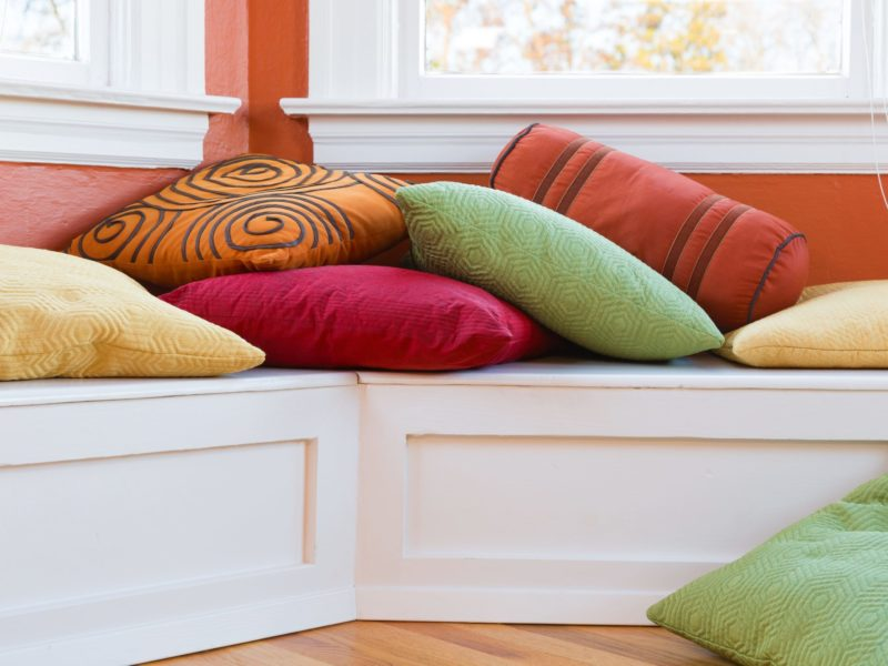 color_pillows_window_seat_decor_AdobeStock_79508864-800x600