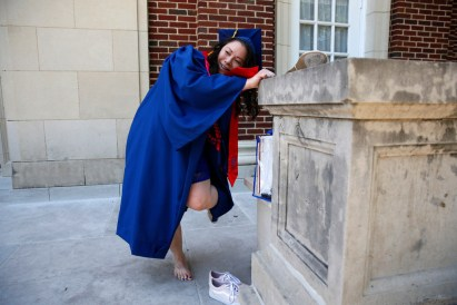 Wendy Birdsall switches shoes before graduation from SMU at McFarlin Auditorium on Friday.(Nathan Hunsinger/Staff Photographer)