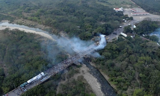 Aerial picture showing demonstrators and smoke billowing from trucks which were carrying humanitarian aid and which were set ablaze on the Francisco de Paula Santander International Brige between Cucuta in Colombia and Urena (R) in Venezuela, on February 23, 2019. - A truck loaded with humanitarian aid was set ablaze on Saturday on the Colombia-Venezuela border, an opposition deputy told reporters amid rioting on the Santander bridge crossing.(EDINSON ESTUPINAN/AFP/Getty Images)