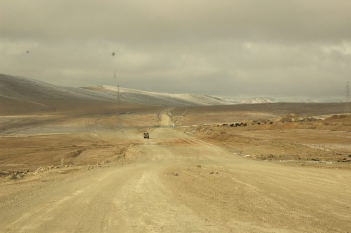 Dusty road in a desert landscape with a car