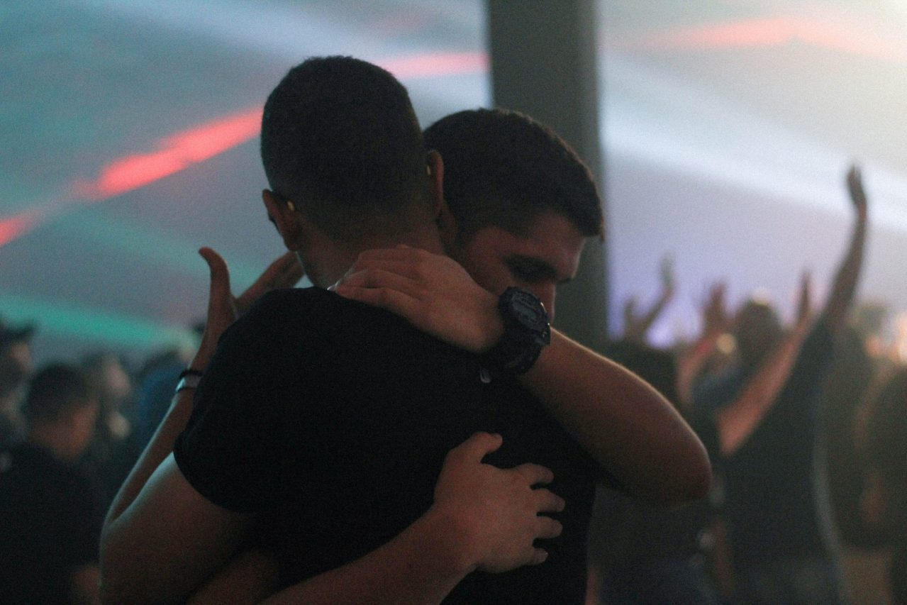 two men hugging in what looks like a dance floor
