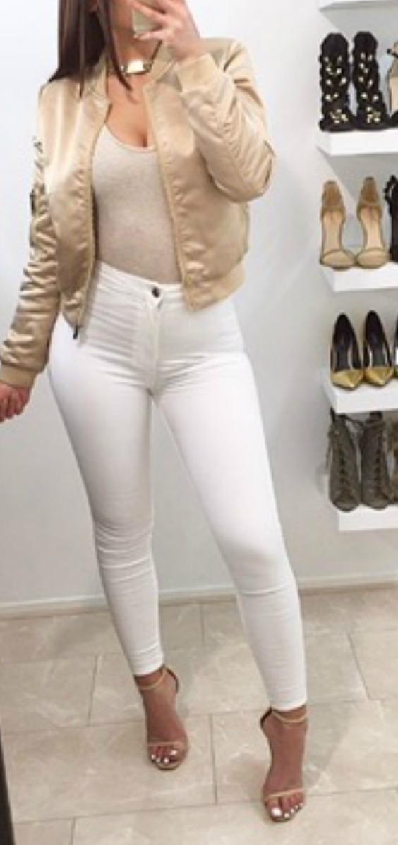 a women wearing a gold satin bomber jacket with white jeans and heels