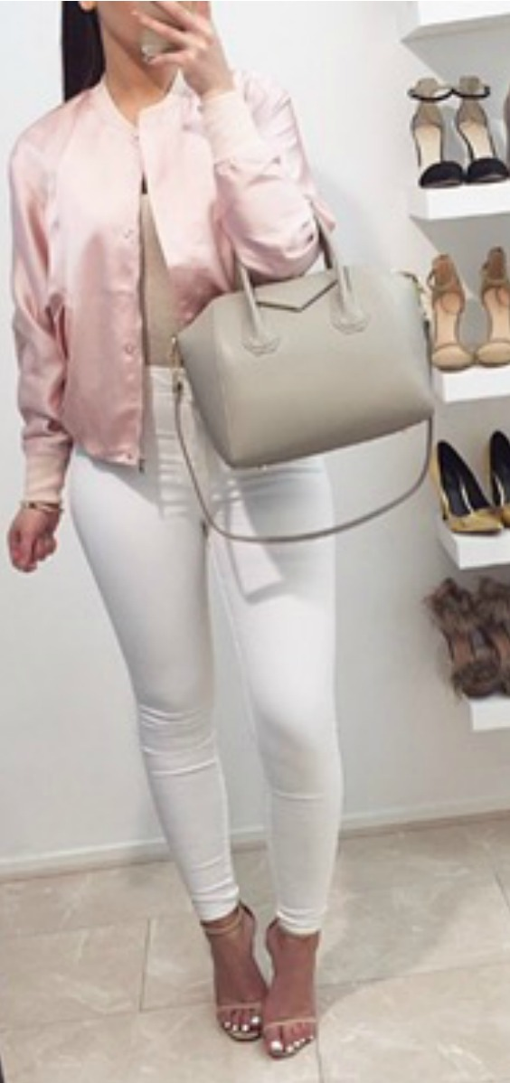a women wearing a pink satin bomber jacket with white jeans and heels