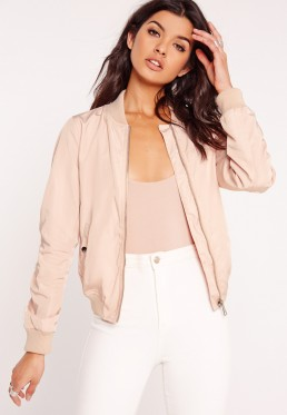 a women wearing a nude bomber jacket with a bodysuit and white jeans
