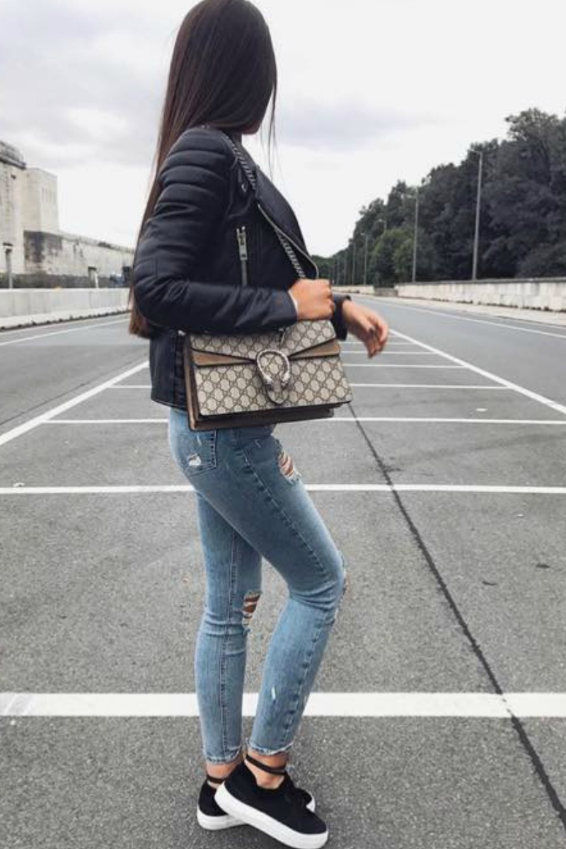 a girl wearing a street style outfit with blue jeans black creepers a black leather jacket and a gucci bag