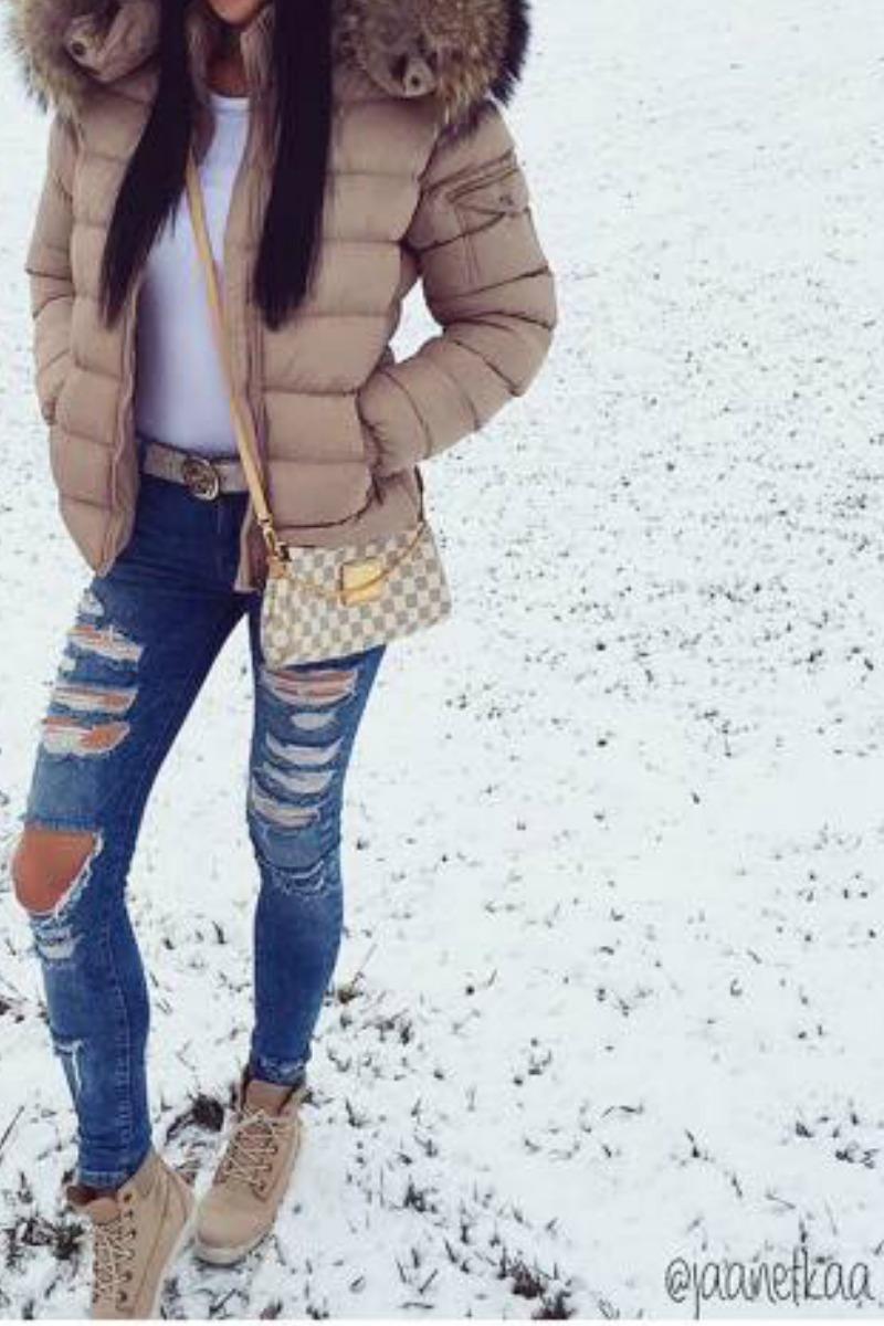 teen girl in the snow wearing ripped blue jeans and a puffy coat