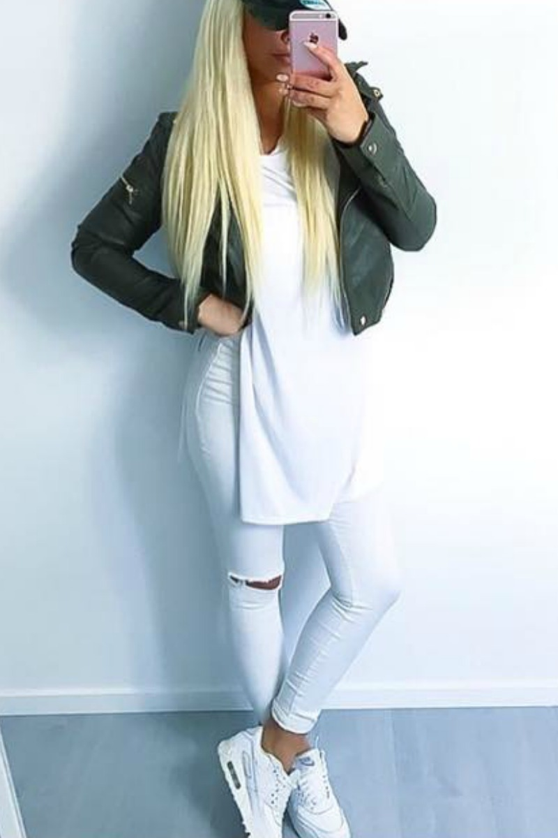 a teen blond girl taking a selfie in a mirror wearing all white with ripped white jeans, white nike sneakers and a green leather jacket
