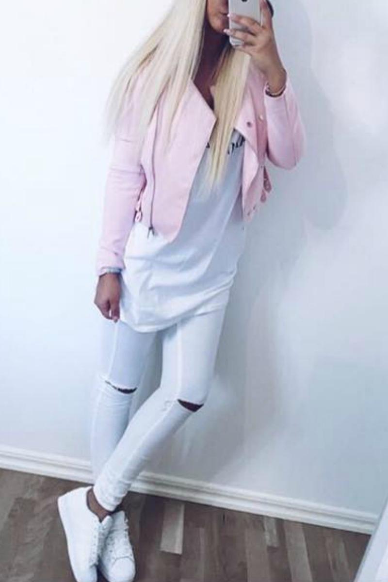 a blond teen with a camera phone taking a picture in the mirror wearing all white with white sneakers and ripped white jeans and a pink leather jacket