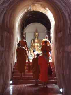 Some monks walking to Buddha in the tunnels of Wat U-Mong