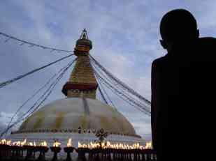 A monk standing beside the butter lamps at Tsamchen gompa