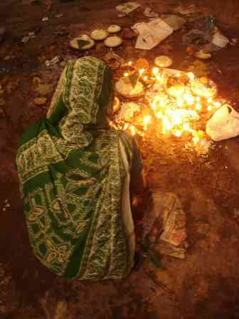 Lighting candles and offering sweets on the street for diwali