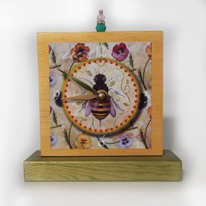 Just Bee Precious Time Shelf Clock has a gold and green wood body with a honey bee surrounded by winter pansies. There is a bead detail at the top.