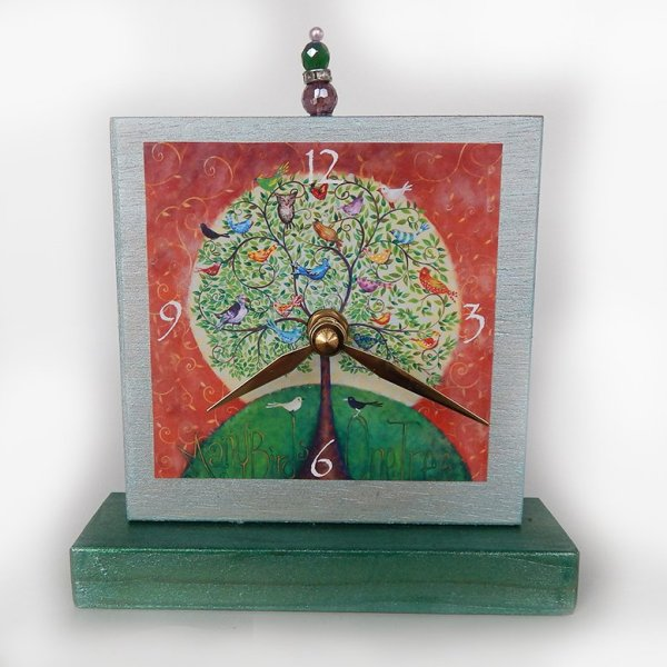 Many Birds Tree Precious Time Shelf Clock is shimmery light blue and forest green paint on wood with an archival print of my Many Birds One Tree painting. There is a bead detail at the top of the clock.