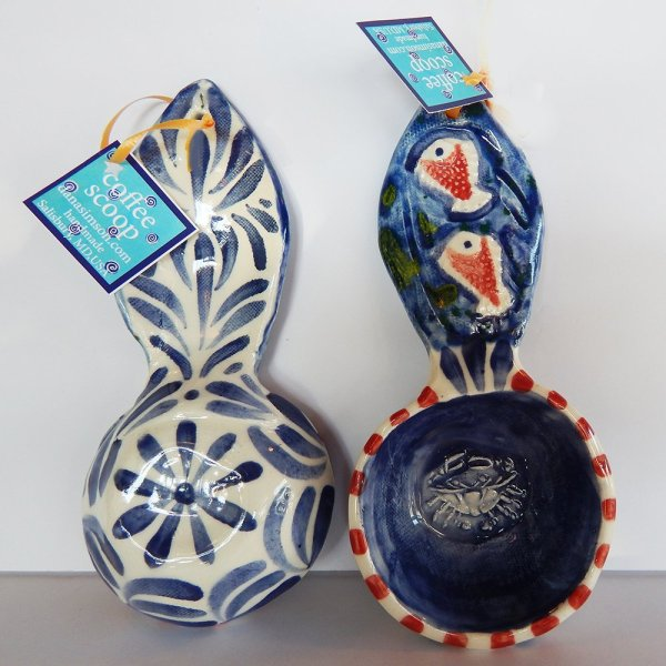 the Blue Crab coffee scoop is red and blue with fish on the handle and a crab inside the scoop- raised images. measures a half cup.