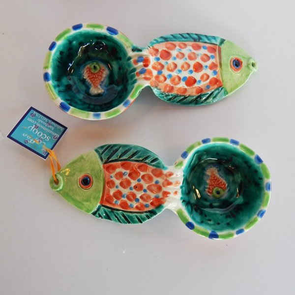 "Our handmade Fish handle Coffee Scoop is about 7 inches by 3,"" in colorful ceramic. The handle is a raised design of a fish. A smaller fish is in the bowl of the scoop."