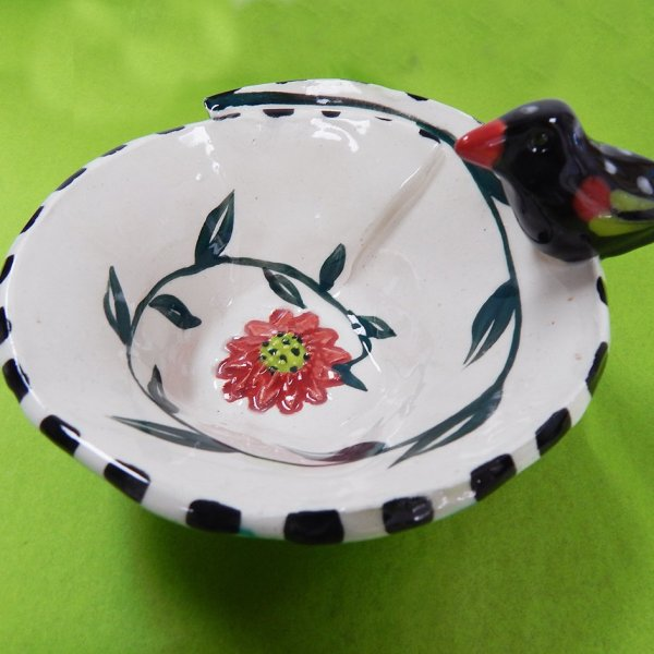 little ceramic bowl with a ceramic bird on edge
