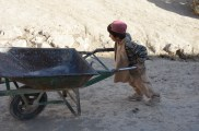 An Afghan boy pushes his wheelbarrow up the street in Jamalkhel