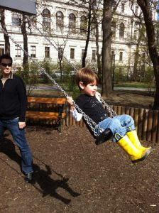 A boy on a playground swing, his dad helping.