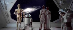 C-3PO, R2D2, Luke, and Leia looking out the window of a spacecraft at a galaxy at the end of The Empire Strikes Back.
