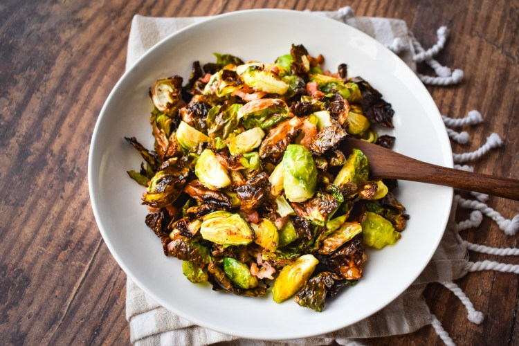 Brussels Sprouts in a white bowl on a wooden table