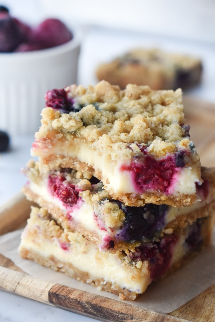 Stack of Blueberry Cream Cheese Bars; the top one with a bite out of it