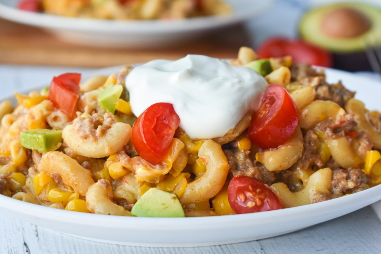 Mexican Mac & Cheese with sour cream, tomatoes and sour cream on top on a white plate
