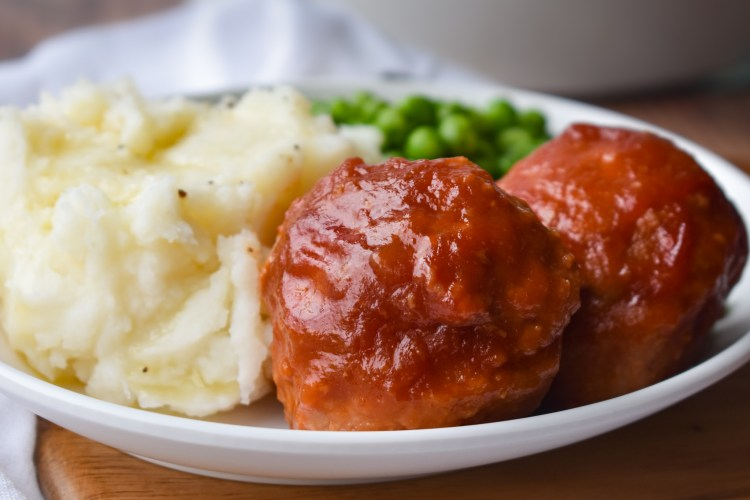 Ham balls on a white plate with mashed potatoes and peas