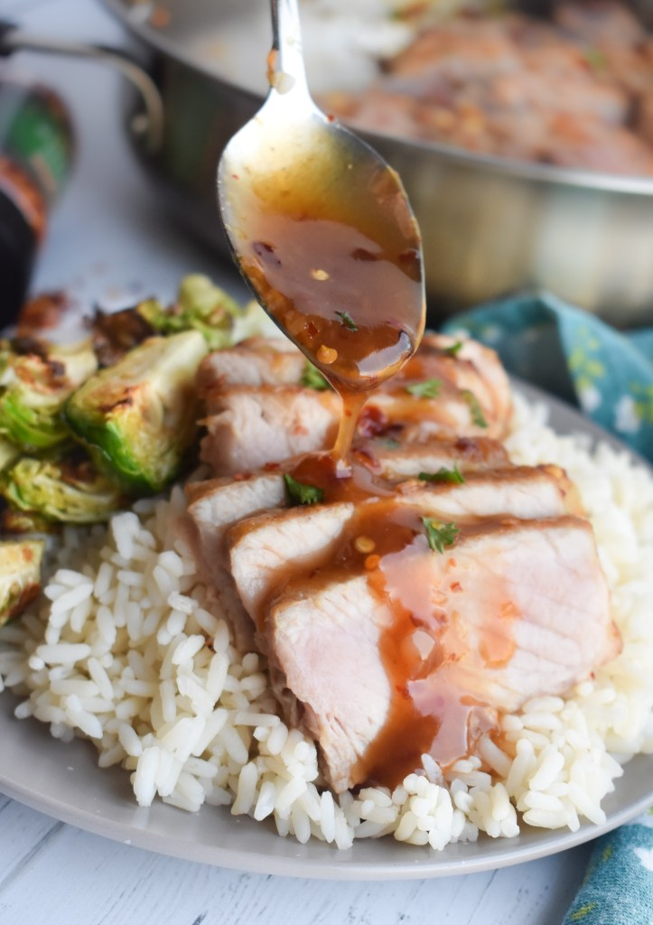 Sliced honey garlic pork chop over rice with sauce being drizzled on top