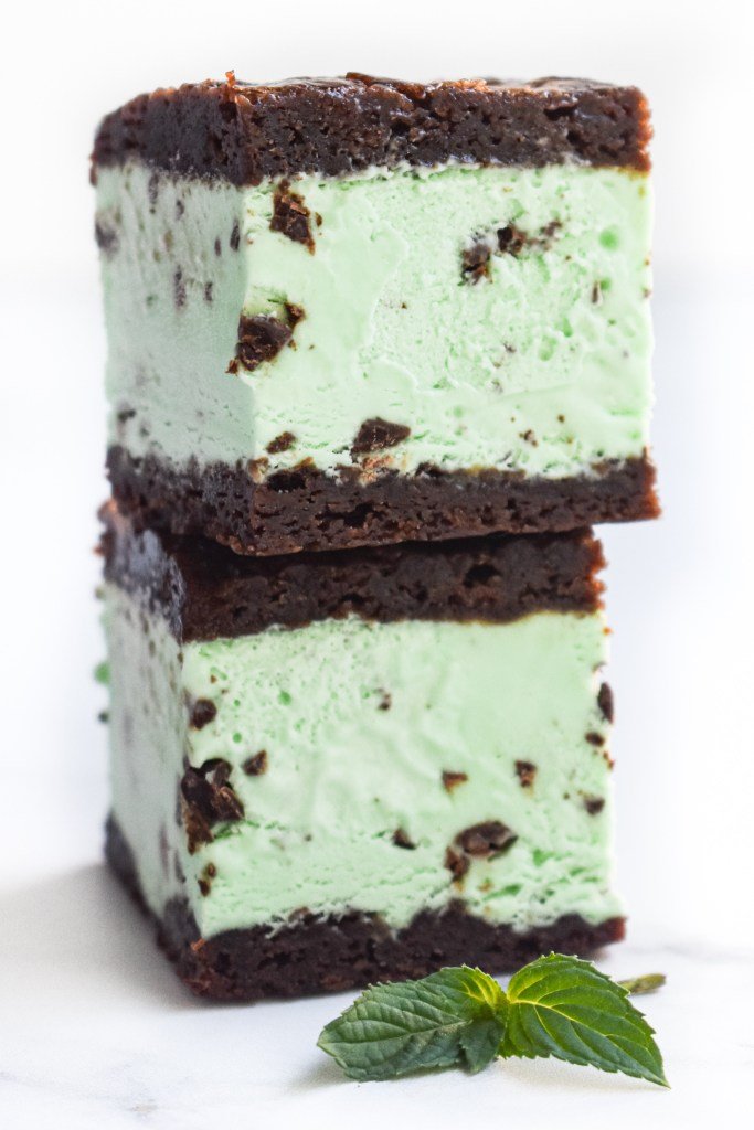 Chocolate Mint Brownie Ice Cream Sandwiches stacked on a white countertop