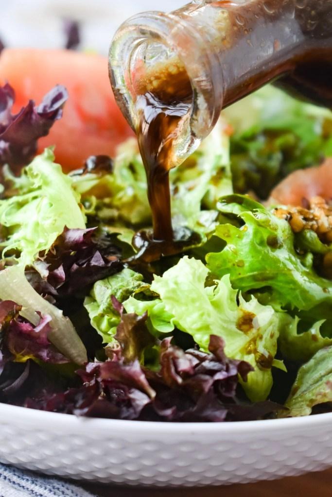 Balsamic Vinaigrette being poured onto a green salad