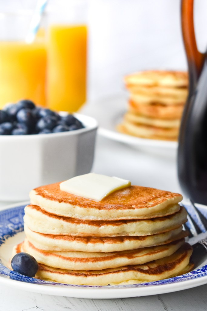 Stack of pancakes with blueberries and orange juice in the background