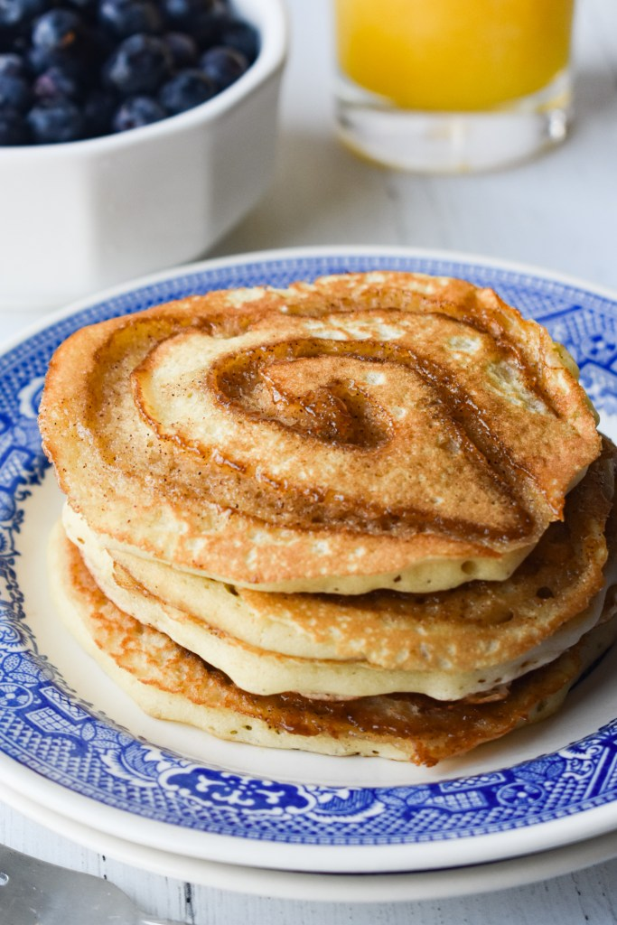 Stack of cinnamon roll pancakes with orange juice and blueberries in the background