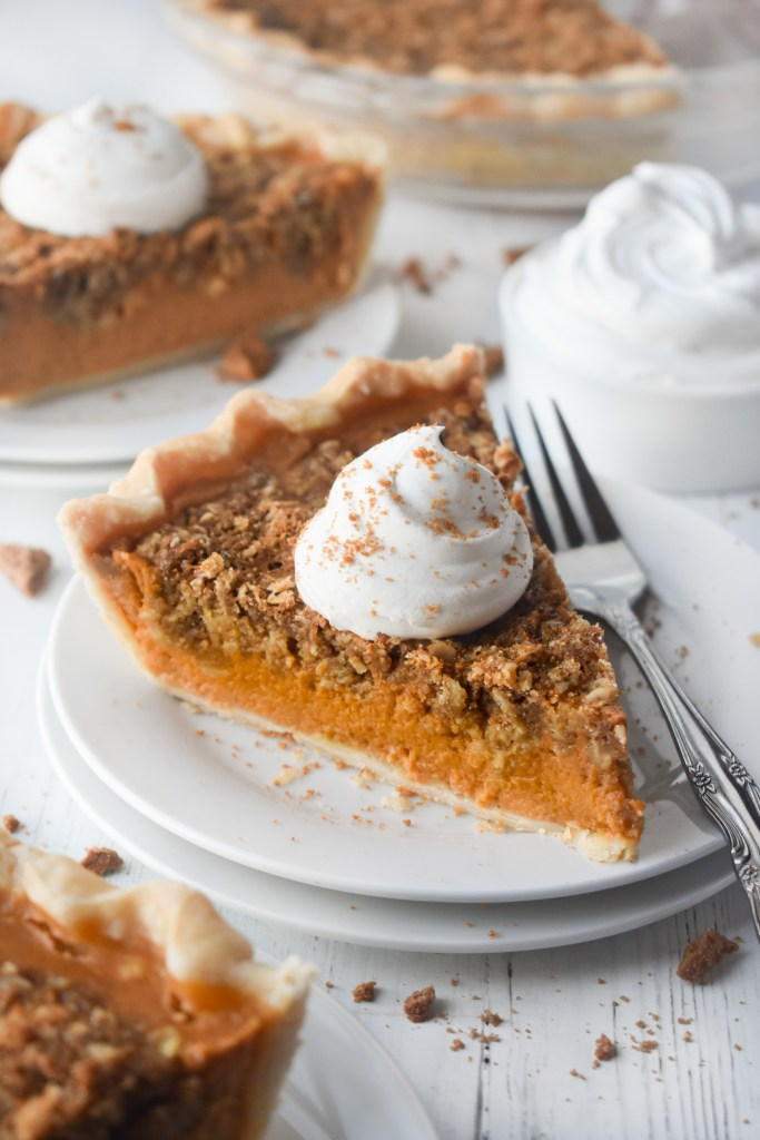 Pumpkin Streusel Pie with whipped topping on a white plate