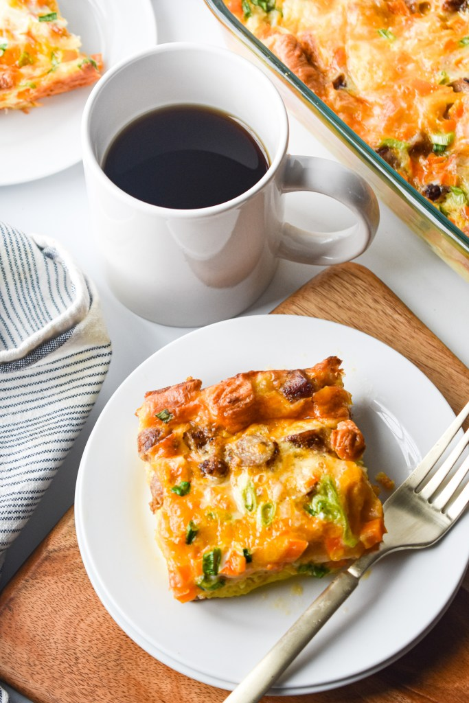 White plate with a piece of breakfast casserole and a cup of coffee