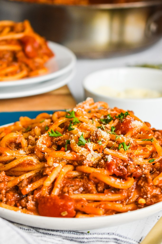 Close-up of spaghetti in meat sauce on a white plate