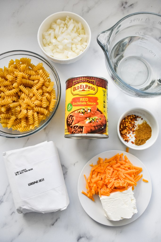 Ingredients needed for the One Pot Enchilada Pasta laid out on a white surface.