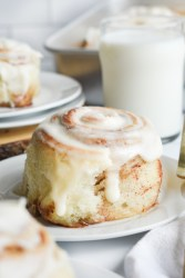 Cinnamon Roll on a white plate with milk in the background.