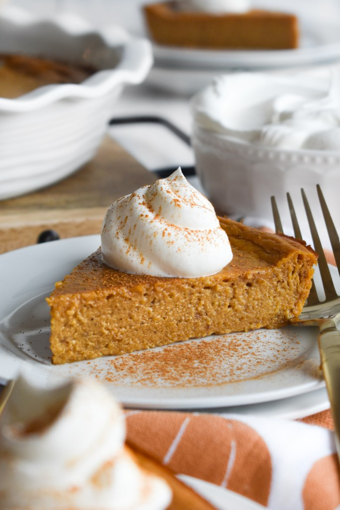 pie on a white plate with whipped topping and a gold fork
