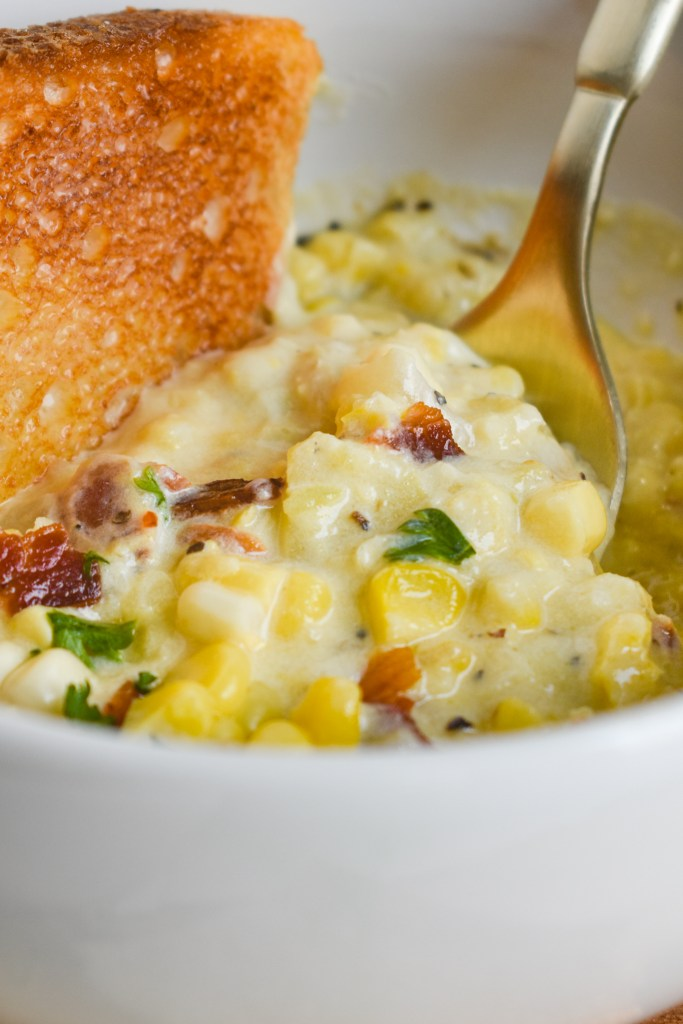 close up of a bowl of corn chowder with a spoon in it