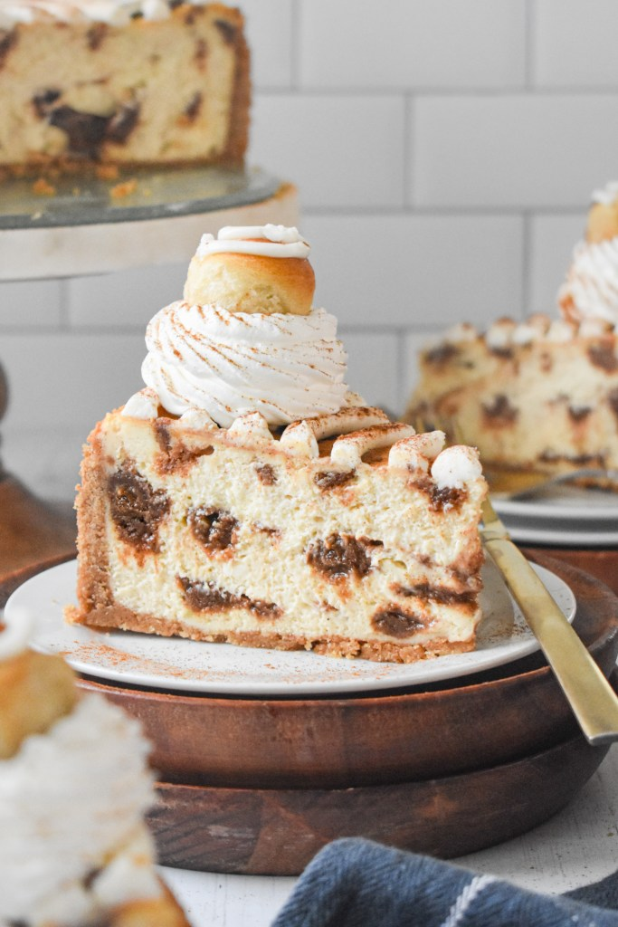 slice of cinnamon roll cheesecake on a white plate with a gold fork and a cheesecake platter in the background
