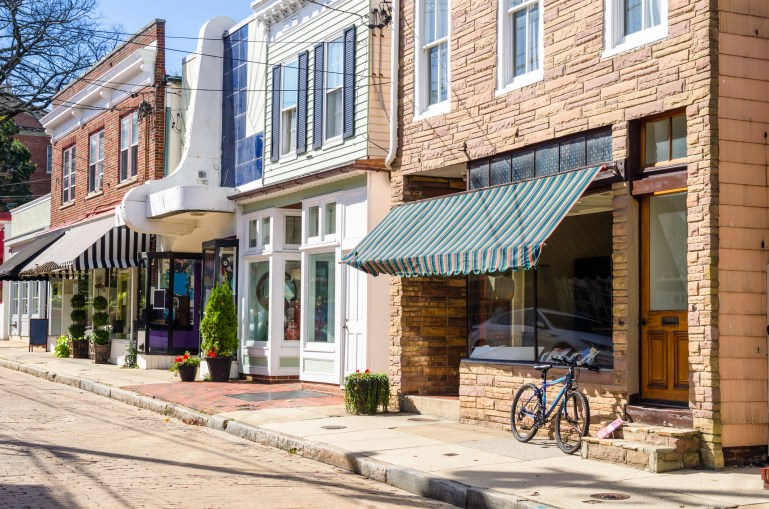 Traditional American Stores along a Cobblestone Street in the Historic District of Annapolis, MD, on a Sunny Autumn Day. There is a Bicycle Leaning against the Window of one of the Stores.