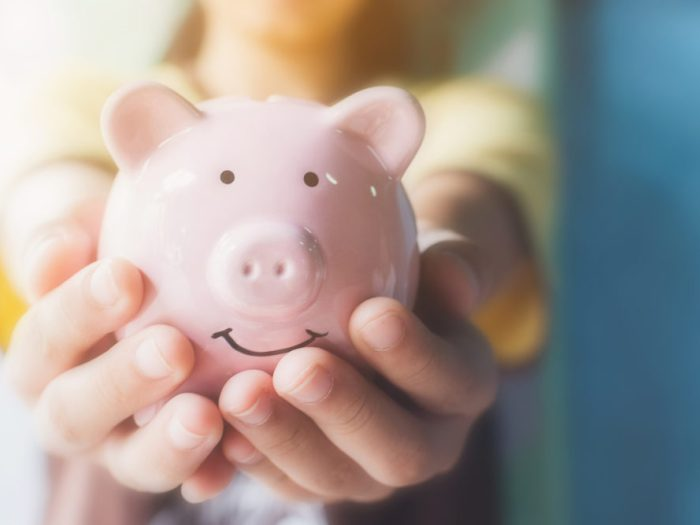 Female hand holding piggy bank. Save money by making year-end tax moves