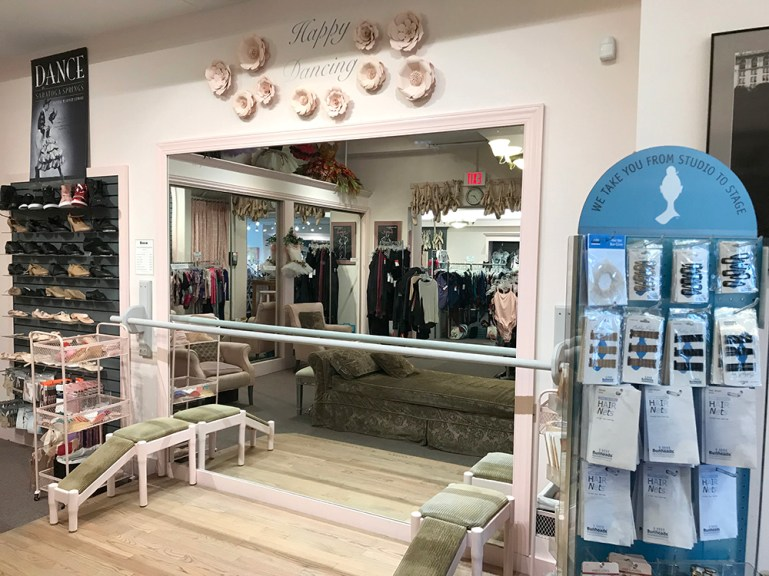 """Pointe shoe fitting area at Saratoga Dance, Etc. store, with mirror, barre and benches. Bunheads rack to the right. """"Happy Dancing"""" graphic with giant flowers on wall."""