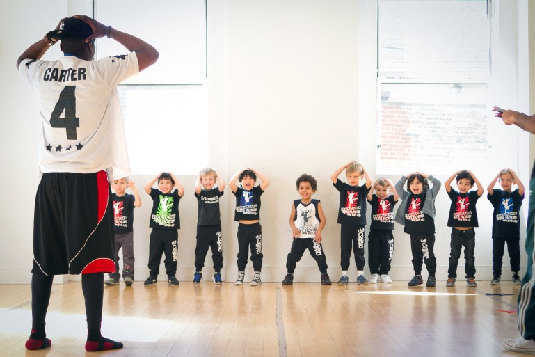 African-American male dance teacher with a row of young boys taking class at Downtown Dance Factory.