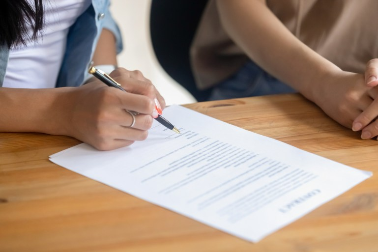 Close up of a woman signing a business contract, such as a nondisclosure agreement.