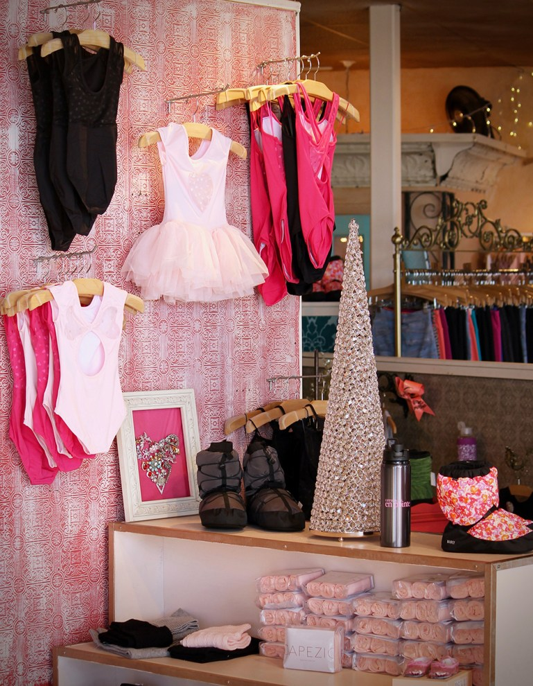 A Valentine's Day feature wall, with racks of pink and red leotards at Attitudes Dancewear, Etc. Below it a display of warm-up booties with a small silver tabletop Christmas tree.