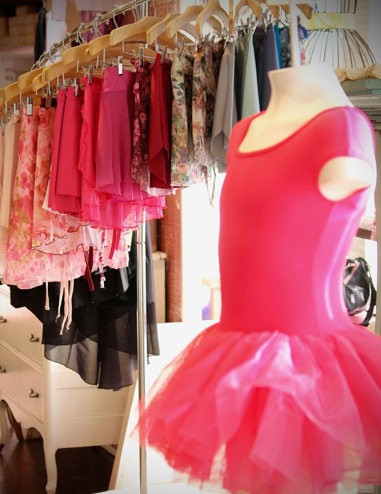 A waterfall rack of dance skirts at Attitudes Dancewear, Etc., many in Valentine's Day pink. In front, a  mannequin, also in bright pink leotard and tutu.