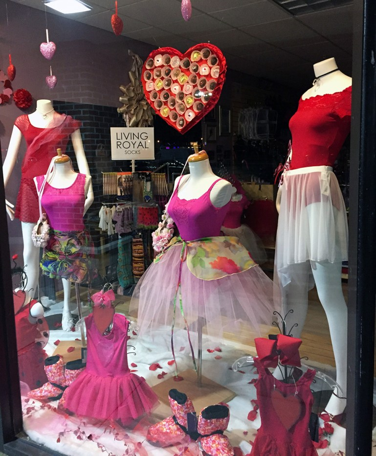 Store window for Valentine's Day at Dance in Dancewear, with pink and red leotards. A heart-shaped prop, which looks like a box of chocolates, hangs above.