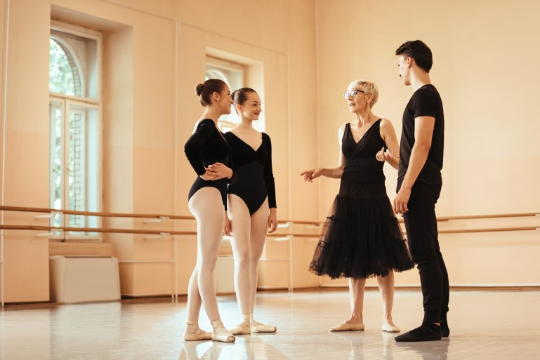 Mature ballet instructor holding a class to group of ballet dancers and communicating with them at ballet studio.