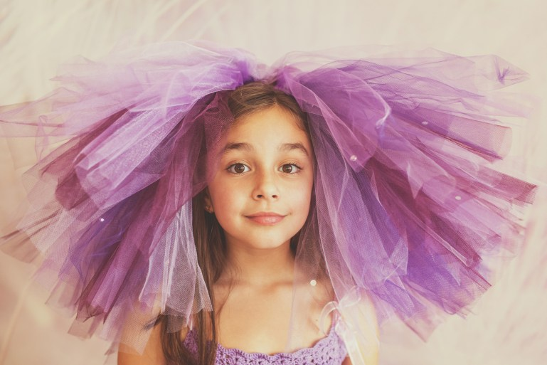 Girl wearing purple tulle skirt on her head, as a hat, with a playful expression on her face.